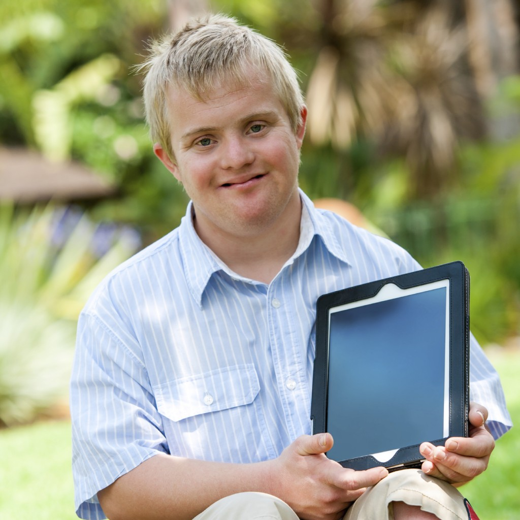 Boy with Down syndrome holding a tablet PC outdoors.