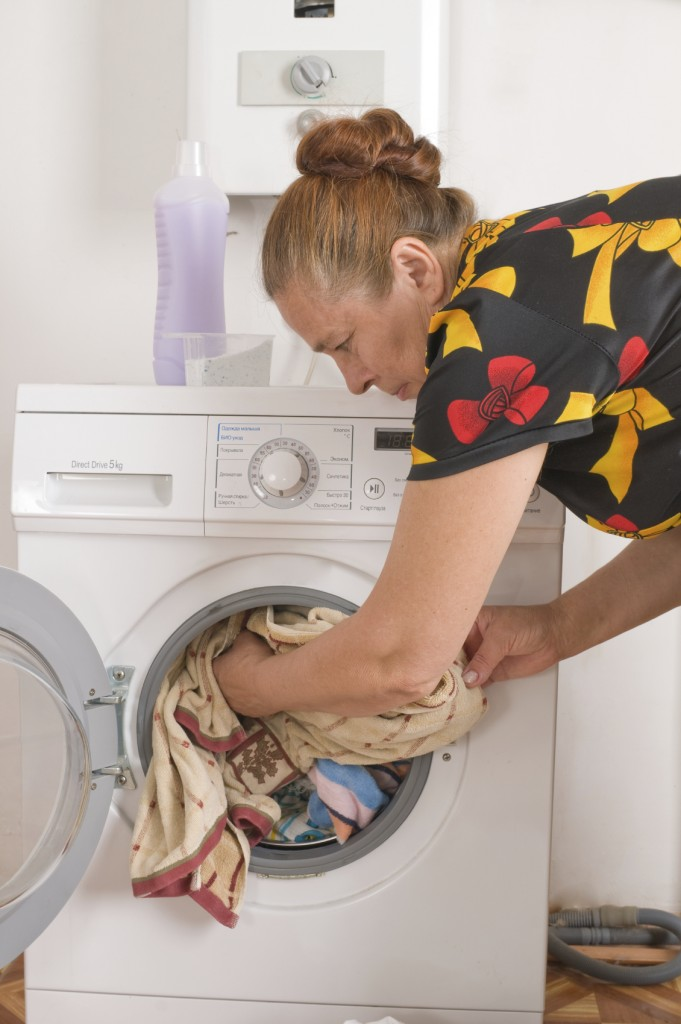The woman loads linen into a washing machine.