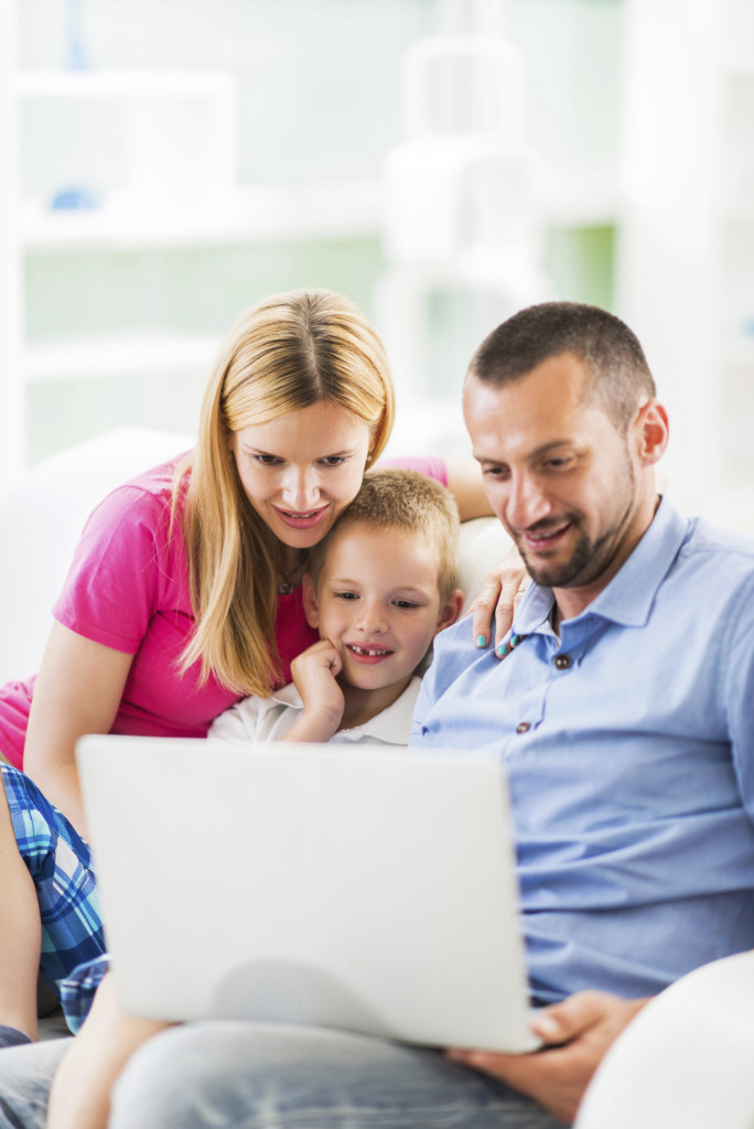 Happy mid adult parents teaching their son how to use a computer.
