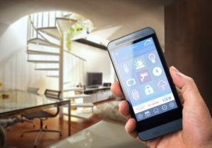 Smarttelefon med smarthusapplikasjon på skjermen. I bakgrunnen stue med en trapp opp.