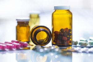 Forskjellige fargerike medisiner i glass og brett