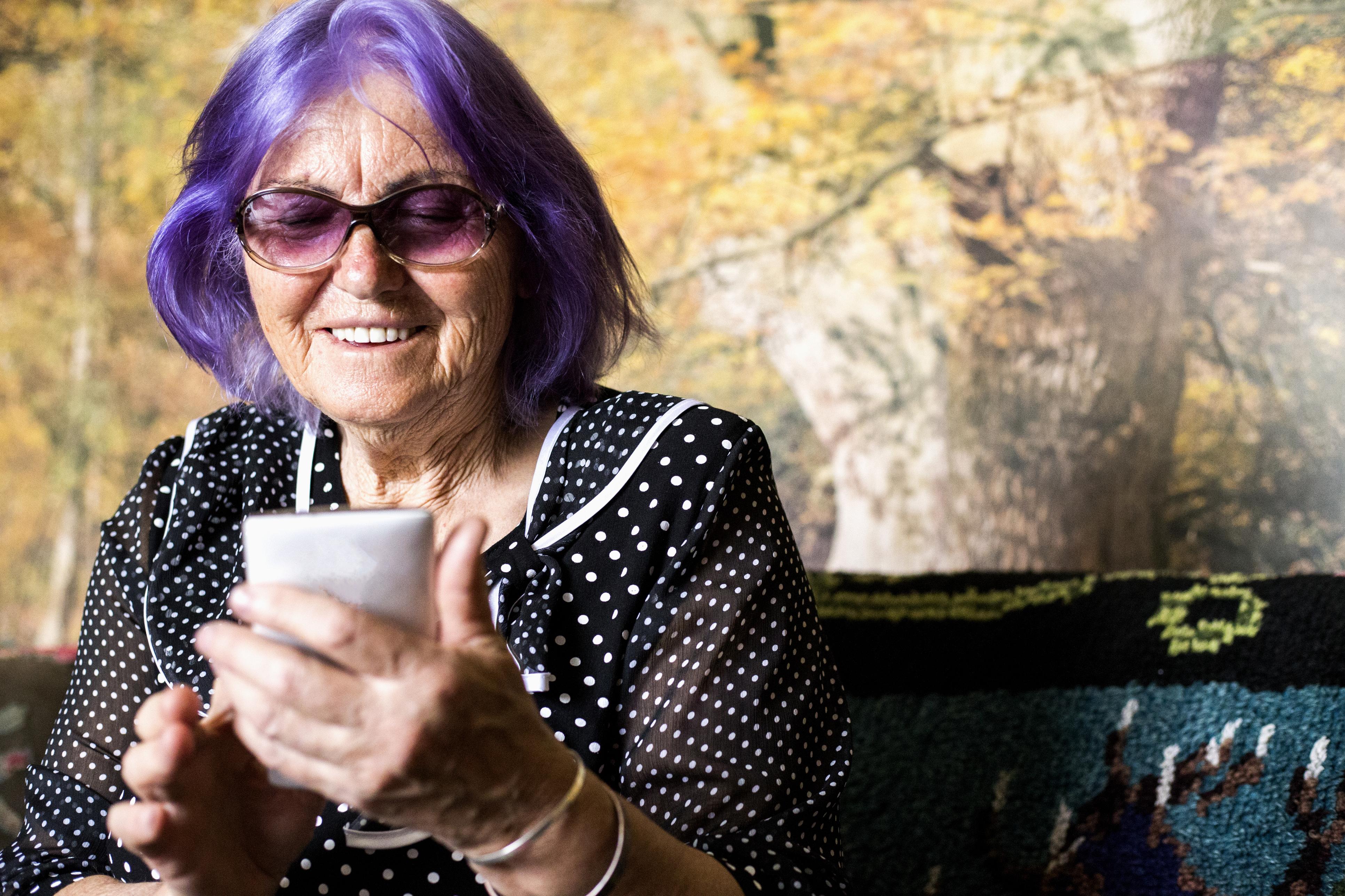 Eldre dame med violett hår smarttelefon i hånden.