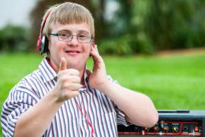 """Ung mann med Down syndrom hører på musikk og viser """"like"""" med tommelen"""