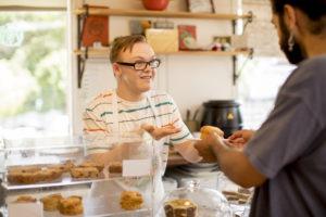 Smilende cafeansatt serverer bakeverk over disken.