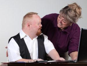 Ung mann og middelaldrende dame på kontoret. Mannen sitter foran en PC, kvinnen står og veileder. Begge smiler bredt.