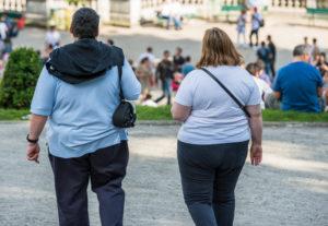 To overvektige, ganske unge mennesker spaserer i en by. De vises bakfra.