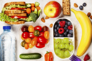 Ferske grønnsaker, frukt, bær, nøtter og en vannflaske.