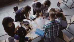 Mange mennesker samlet rundt et møtebord i gruppearbeid.