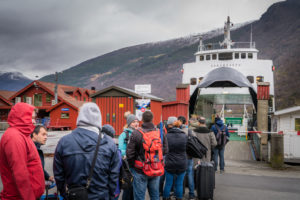 Mange mennesker i ferd med å gå ombord på en ferge i et fjellandskap.