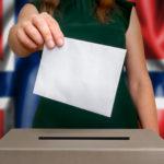 Kvinnens hånd dropper stemmeseddelen i konvolutt inn i valgurnen