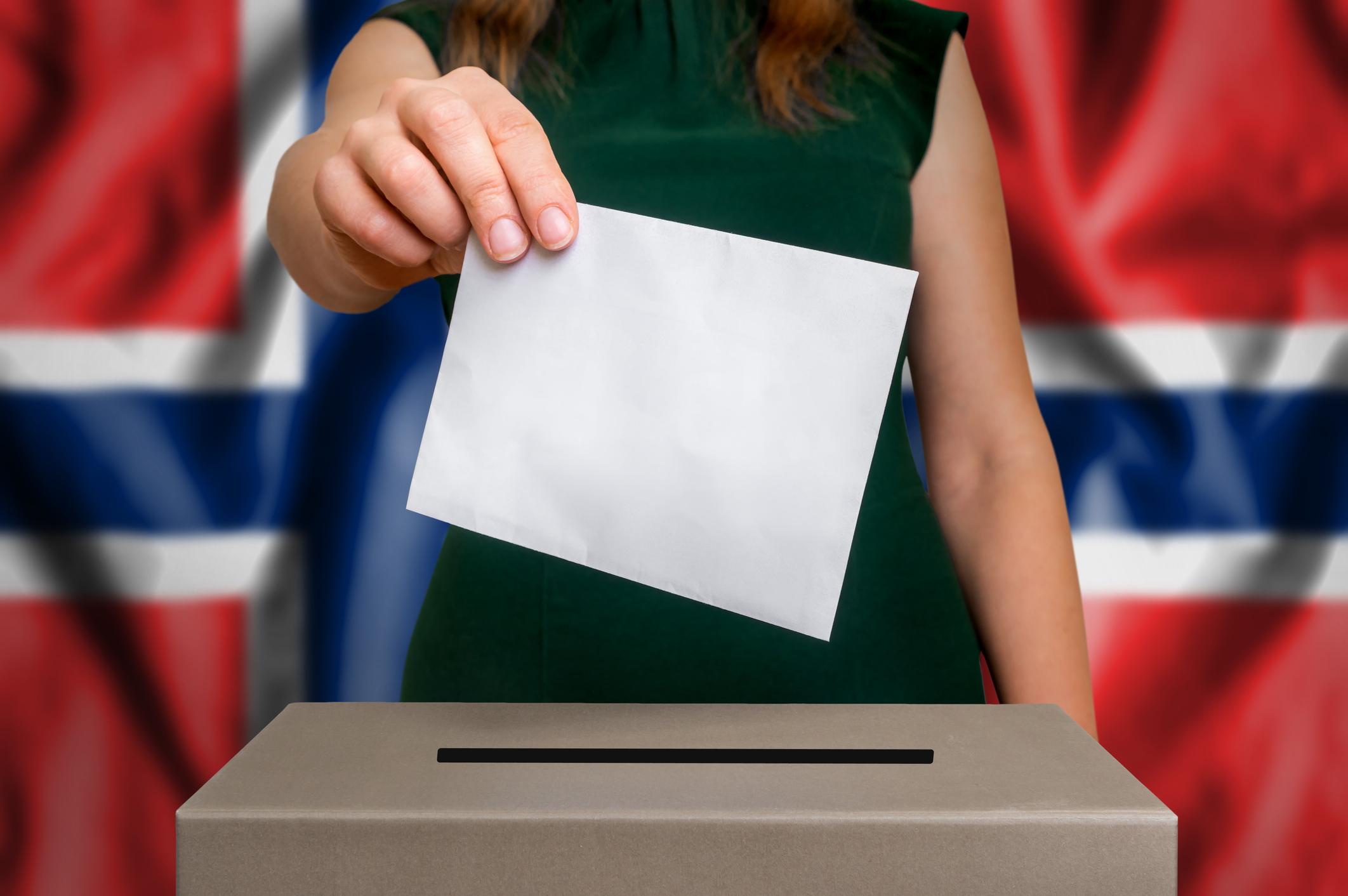 Kvinne som legger valgseddelen inn i valgurnen. Norsk flagg i bakgrunnen.