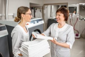 To kvinner i et vaskeri med rent lintøy i hendene