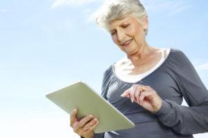 Eldre sporty kvinne ute med et nettbrett