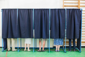 Mennesker som står bak gardinen i et valgavlukke
