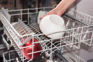 Hånd som plasserer en bolle i oppvaskmaskinen