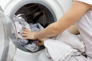 Hender som fyller vaskemaskinen med tøy