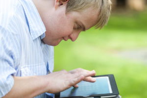 Ung mann med utviklingshemning bruker nettbrett