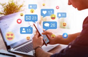 Hender som holder en mobiltelefon, PC i bakrunnen. I luften henger symboler fra sosiale medier.