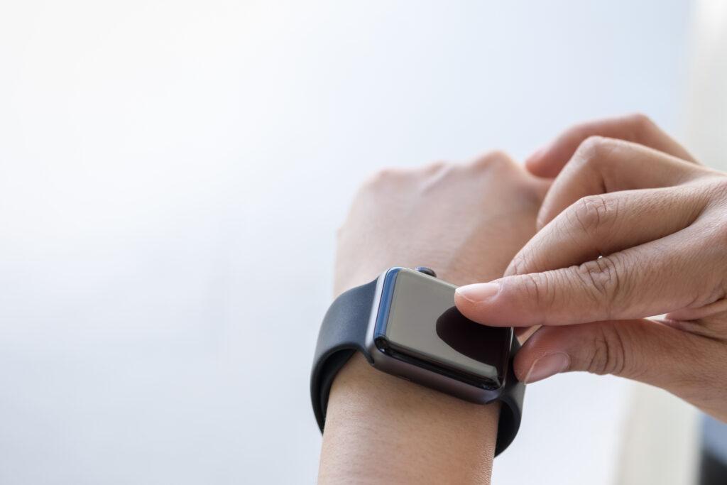 Hånd som trykker på skjermen til en sportsklokke