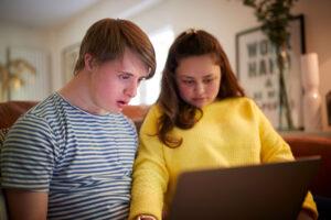 Ungt par med Down syndrom ser på PC-skjerm sammen